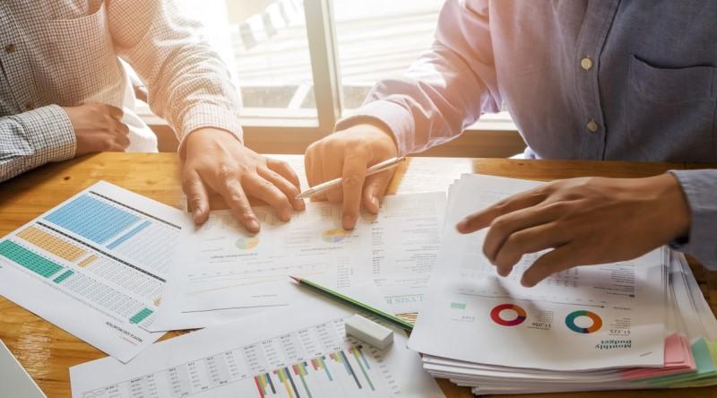 Geschäftsführer und Anzeigenleiter bei einem Fachverlag besprechen die Umsatzentwicklung.