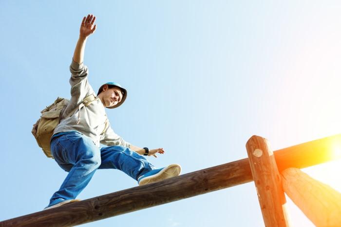 Ein Mann balanciert auf einem Balken als Symbolbild für die Gratwanderung bei der Erstellung eines Mediaplans